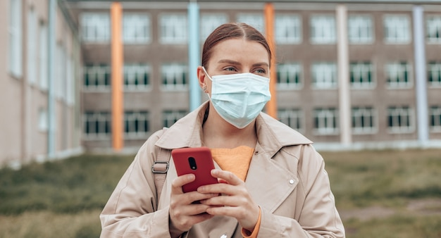 Portret van een stijlvol jong meisje met een medisch gezichtsmasker met moderne smartphone in het universiteitspark