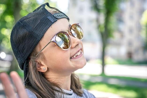 Portret van een stijlvol klein meisje in zonnebril buitenshuis.