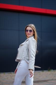 Portret van een stijlvol langharig meisje in een witte blouse en lichte spijkerbroek staat met een glimlach tegen de achtergrond van een grijze muur van een gebouw op een zonnige lentedag.