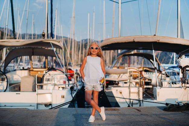 Portret van een stijlvol meisje in de buurt van de zee in een jachtclub. meisje op de pier bij het jacht parkeerplaats.