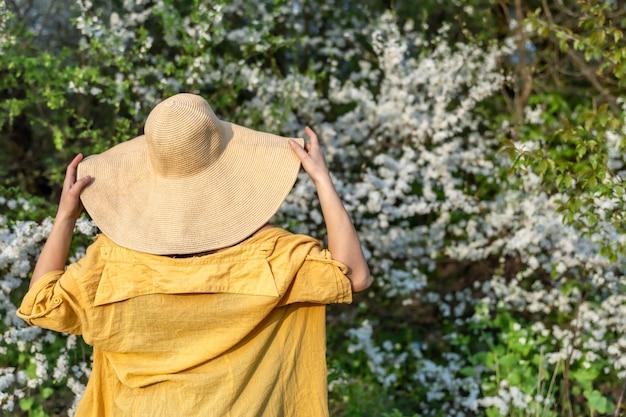 Portret van een stijlvol meisje in een hoed tussen bloeiende lentebomen in het bos.