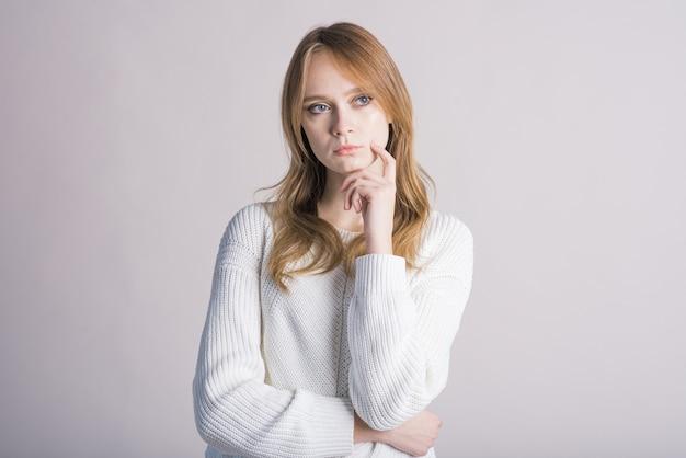 Portret van een stijlvol meisje op een witte achtergrond in de studio die denkt