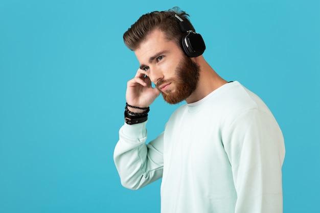 Portret van een stijlvolle, aantrekkelijke jonge, bebaarde man die naar muziek luistert op een draadloze hoofdtelefoon in moderne stijl zelfverzekerde stemming