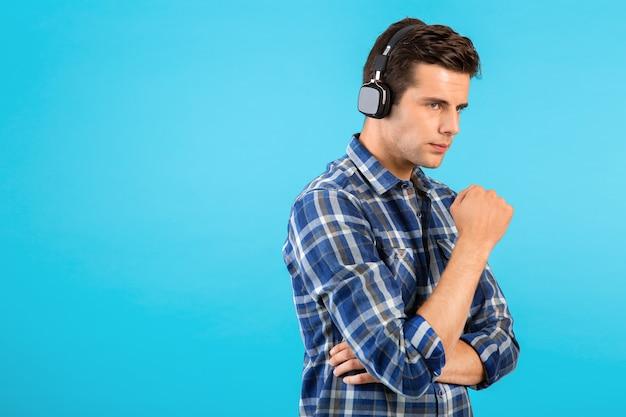 Portret van een stijlvolle, aantrekkelijke, knappe jongeman die naar muziek luistert op een draadloze koptelefoon met een leuke moderne stijl, een gelukkige emotionele stemming