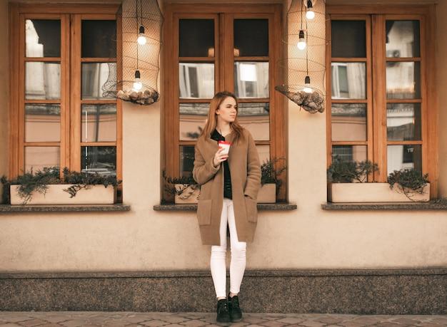 Portret van een stijlvolle dame van volledige lengte, staande met een kopje koffie in haar handen, gekleed in een jas tegen de achtergrond van de muur van het café, zijwaarts kijkend