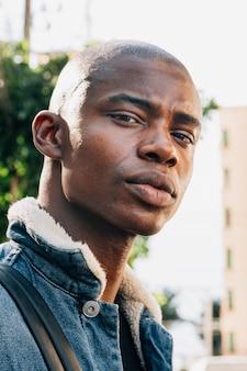 Portret van een stijlvolle geschoren afrikaanse jonge man kijkt naar de camera