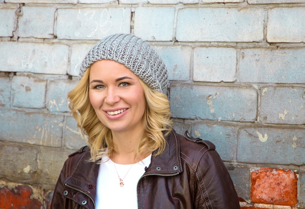 Portret van een stijlvolle jonge hipster vrouw in de straten van de stad.