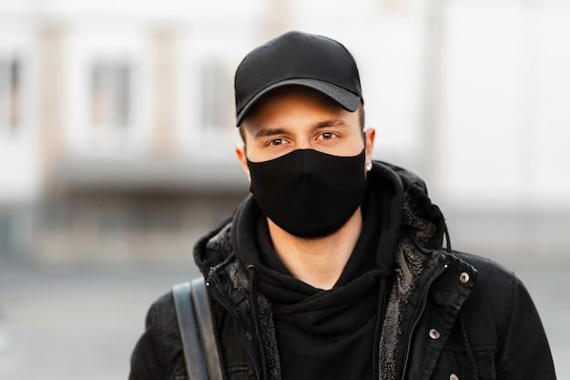 Portret van een stijlvolle jonge kerel met een medisch masker en zwarte pet in een modieuze jas en hoodie met een rugzak in de stad