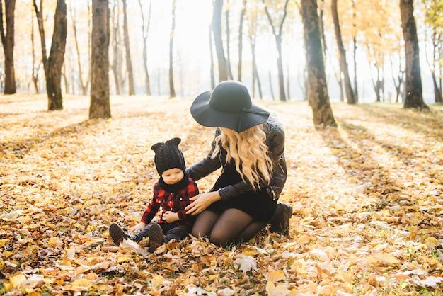 Portret van een stijlvolle jonge moeder met kleine kinderen in de herfstpark.