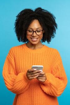 Portret van een stijlvolle jonge vrouw die haar mobiele telefoon doorbladert