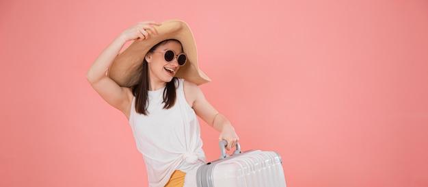 Portret van een stijlvolle jonge vrouw in een hoed met een koffer