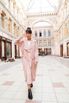 Portret van een stijlvolle jonge vrouw in roze jas
