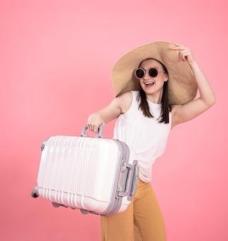 Portret van een stijlvolle jonge vrouw in zomerkleren en een rieten hoed met een koffer op geïsoleerde roze