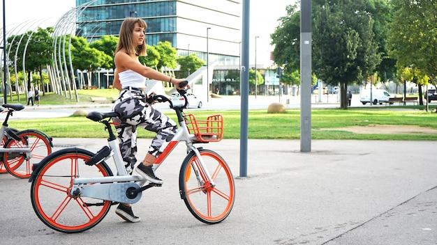 Portret van een stijlvolle jonge vrouw met fiets tegen moderne gebouwen