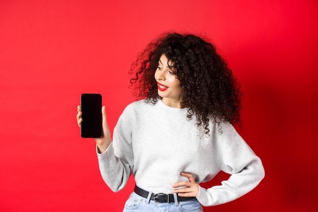 Portret van een stijlvolle jonge vrouw met krullend haar die een leeg smartphonescherm toont, een winkel-app demonstreert, staande op een rode achtergrond