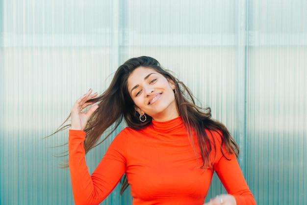 Portret van een stijlvolle jonge vrouw tegen golfplaten achtergrond
