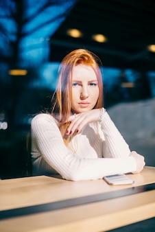 Portret van een stijlvolle jonge vrouw zitten in café