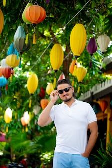 Portret van een stijlvolle jongeman in zonnebril op straat, levensstijl. stedelijke stijl. de man met bril lacht vrolijk