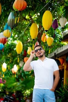 Portret van een stijlvolle jongeman in zonnebril op straat, levensstijl. stedelijke stijl. de man met een bril lacht vrolijk