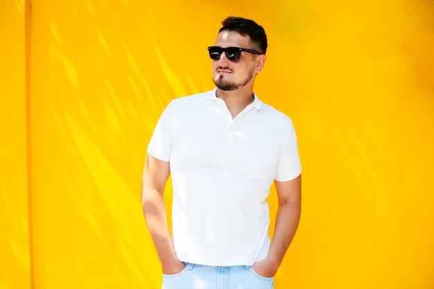 Portret van een stijlvolle jongeman met een baard in zonnebril en een wit t-shirt