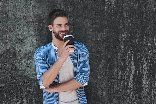 Portret van een stijlvolle knappe jongeman die buiten staat en op de muur leunt met koffie