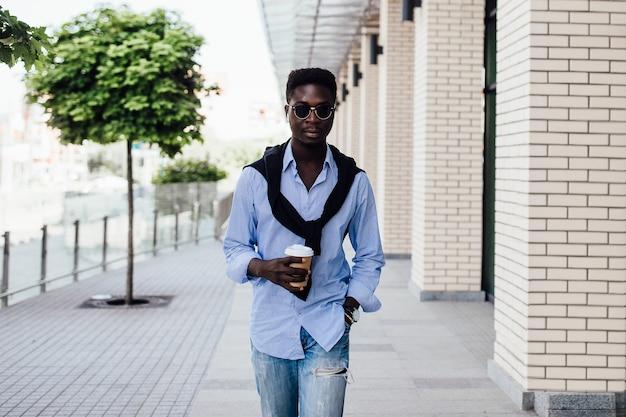 Portret van een stijlvolle knappe jongeman met een jas, zonnebril, shirt en een kopje koffie terwijl hij loopt. informele stijl.