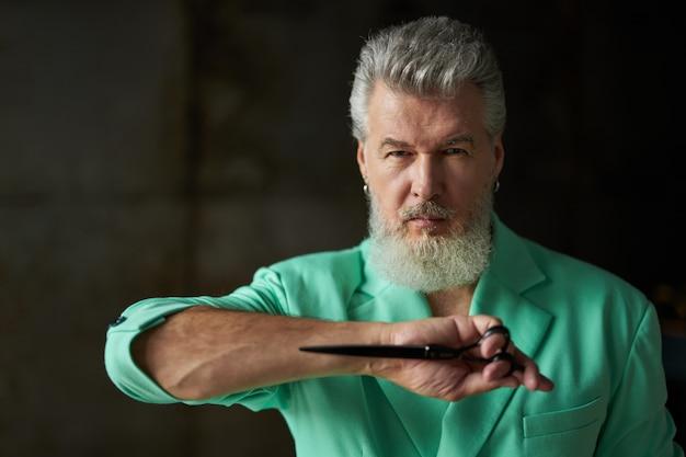 Portret van een stijlvolle, moderne grijsharige volwassen man met baard die een kleurrijke outfit draagt en naar de camera kijkt, een scherpe kappersschaar vasthoudt terwijl hij binnenshuis poseert. beroepsberoepsconcept