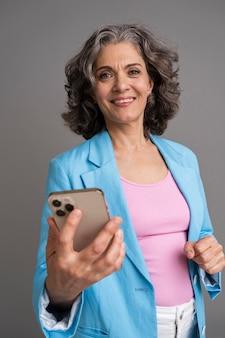 Portret van een stijlvolle senior vrouw die haar telefoon vasthoudt