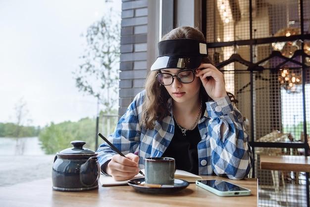 Portret van een stijlvolle vrouw die in een café zit en in een notitieboekje schrijft