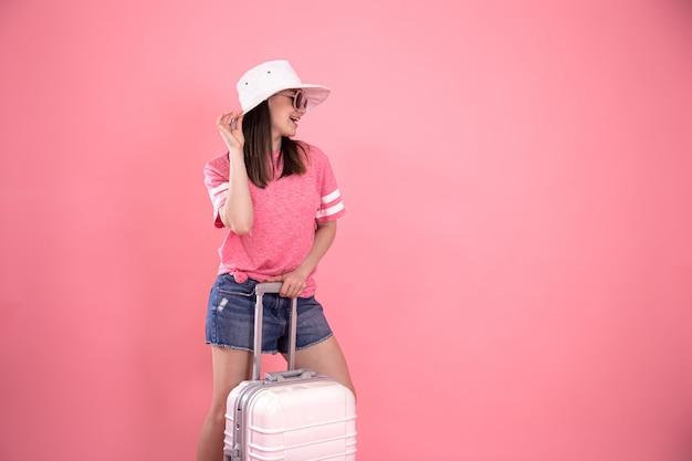 Portret van een stijlvolle vrouw in modieuze zomerkleding en een witte hoed op roze met een koffer om te reizen.