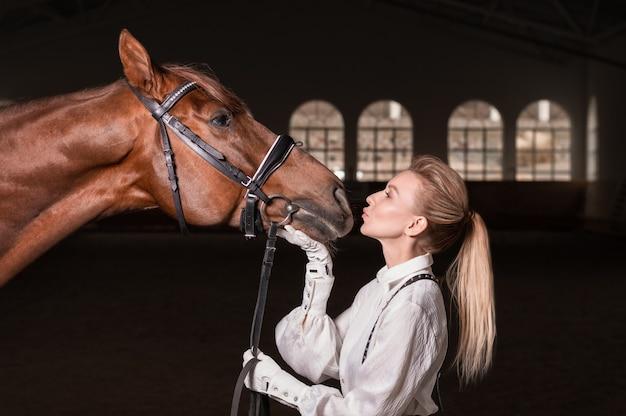 Portret van een stijlvolle vrouw knuffelen een volbloed paard. liefde en zorgconcept. gemengde media