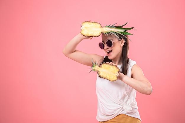 Portret van een stijlvolle vrouw op roze met ananas in haar handen.