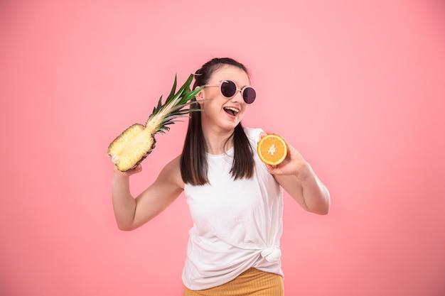 Portret van een stijlvolle vrouw op roze met fruit in haar handen.