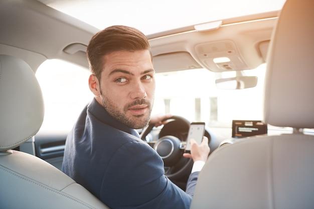 Portret van een stijlvolle zelfverzekerde zakenman in een auto die een pak draagt en zich naar de achterbank draait met een serieuze blik