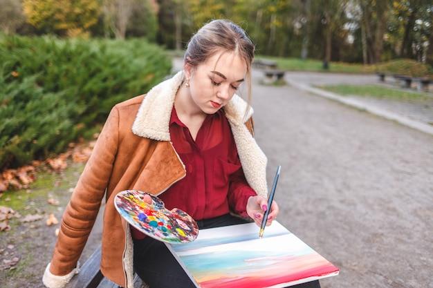 Portret van een straatartiest die in een park op een bankje zit en een schilderij, palet en penseel in haar handen heeft
