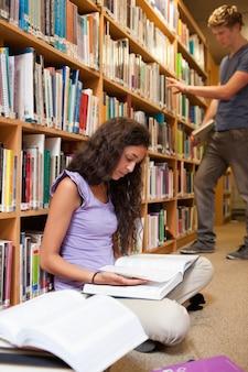 Portret van een student die een boek leest terwijl haar klasgenoot choo is