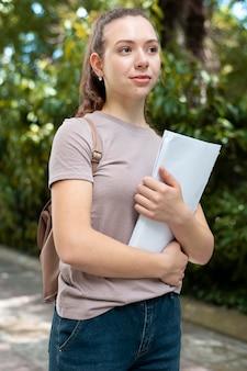 Portret van een student die wat boeken vasthoudt