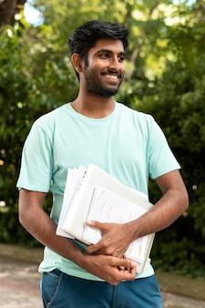 Portret van een student die wat boeken vasthoudt Premium Foto