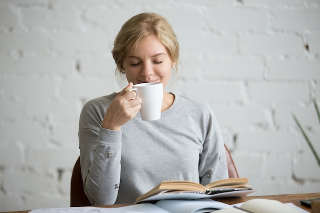 Portret van een student meisje inhalend aroma van haar drankje