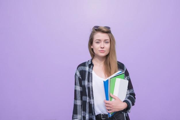 Portret van een studentenmeisje dat zich op een purpere achtergrond met boeken en notitieboekjes in haar handen bevindt en de camera onderzoekt.