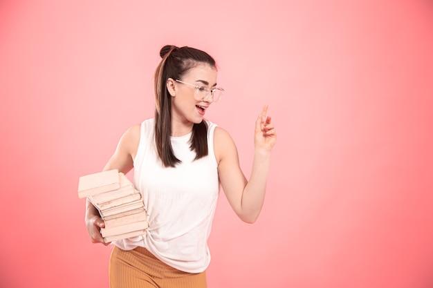 Portret van een studentenmeisje met bril op een roze achtergrond met boeken in haar handen. concept van onderwijs en hobby's.