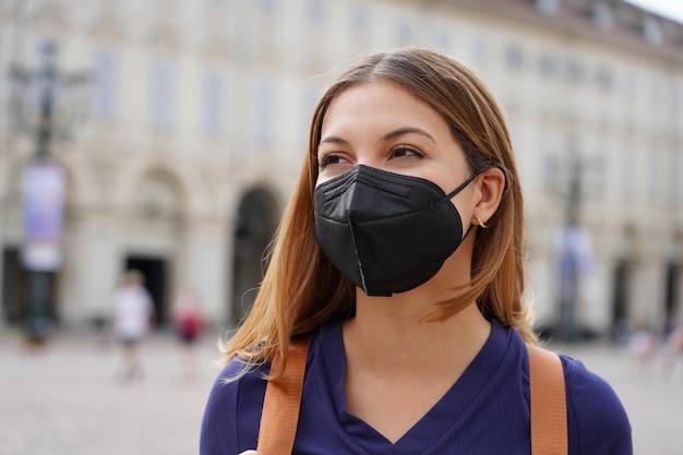 Portret van een studentenmeisje met een beschermend kn95 ffp2 zwart masker dat door de stadsstraat loopt