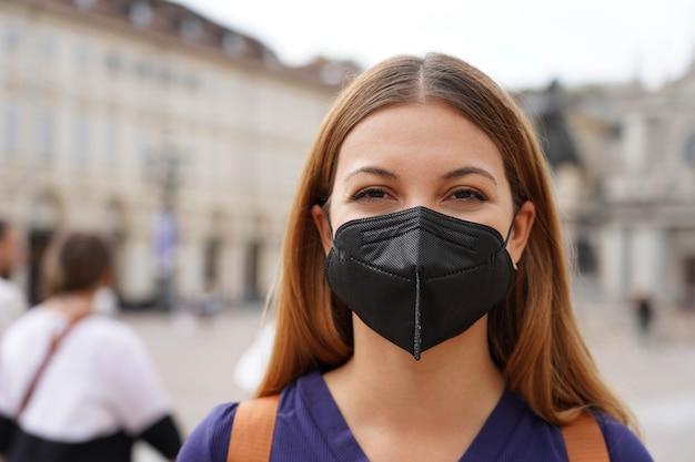 Portret van een studentenmeisje met een beschermend kn95 ffp2 zwart masker dat naar een camera kijkt met een stedelijke achtergrond