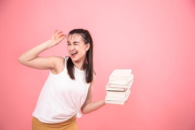 Portret van een studentenmeisje met glazen die met boeken in haar handen stellen. concept van onderwijs en hobby's.
