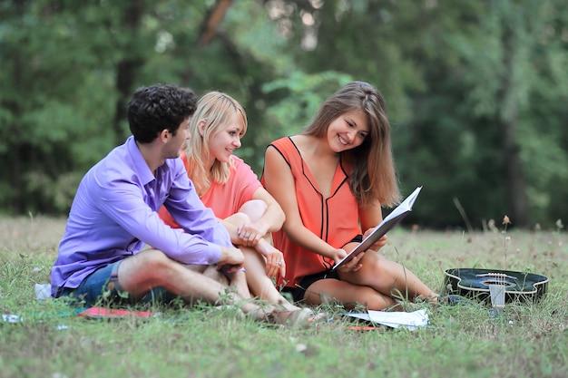 Portret van een studententeam zittend op het gras in het park.