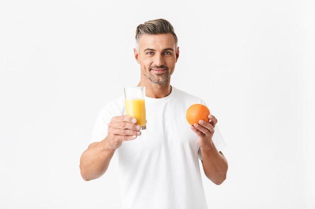 Portret van een succesvolle 30-jarige man met haren in een casual t-shirt met een glas sap en sinaasappelfruit op wit wordt geïsoleerd