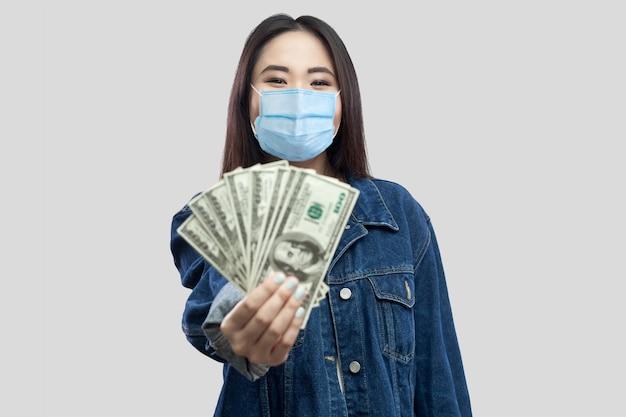 Portret van een succesvolle aantrekkelijke jonge aziatische vrouw met een medisch masker dat staat, dollars vasthoudt, demonstratie geeft en naar de camera kijkt met een glimlach. binnen, studio-opname, geïsoleerd, grijze achtergrond