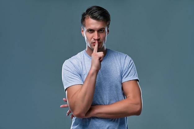 Portret van een succesvolle aantrekkelijke serieuze man geïsoleerd op een grijze achtergrond met een teken van stilte gebaar vinger in de mond steken.