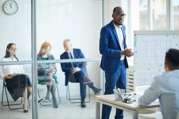 Portret van een succesvolle afro-amerikaanse zakenman permanent door whiteboard tijdens de presentatie van ontwerpproject tijdens bijeenkomst in kantoor, kopieertempo