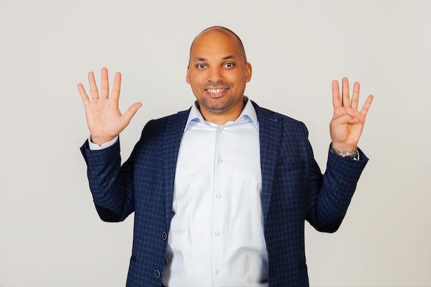 Portret van een succesvolle jonge afro-amerikaanse zakenman man, met vingers tonen aan nummer negen, glimlachend, zelfverzekerd en gelukkig. de man toont negen vingers. nummer 9. staande op een grijze muur.